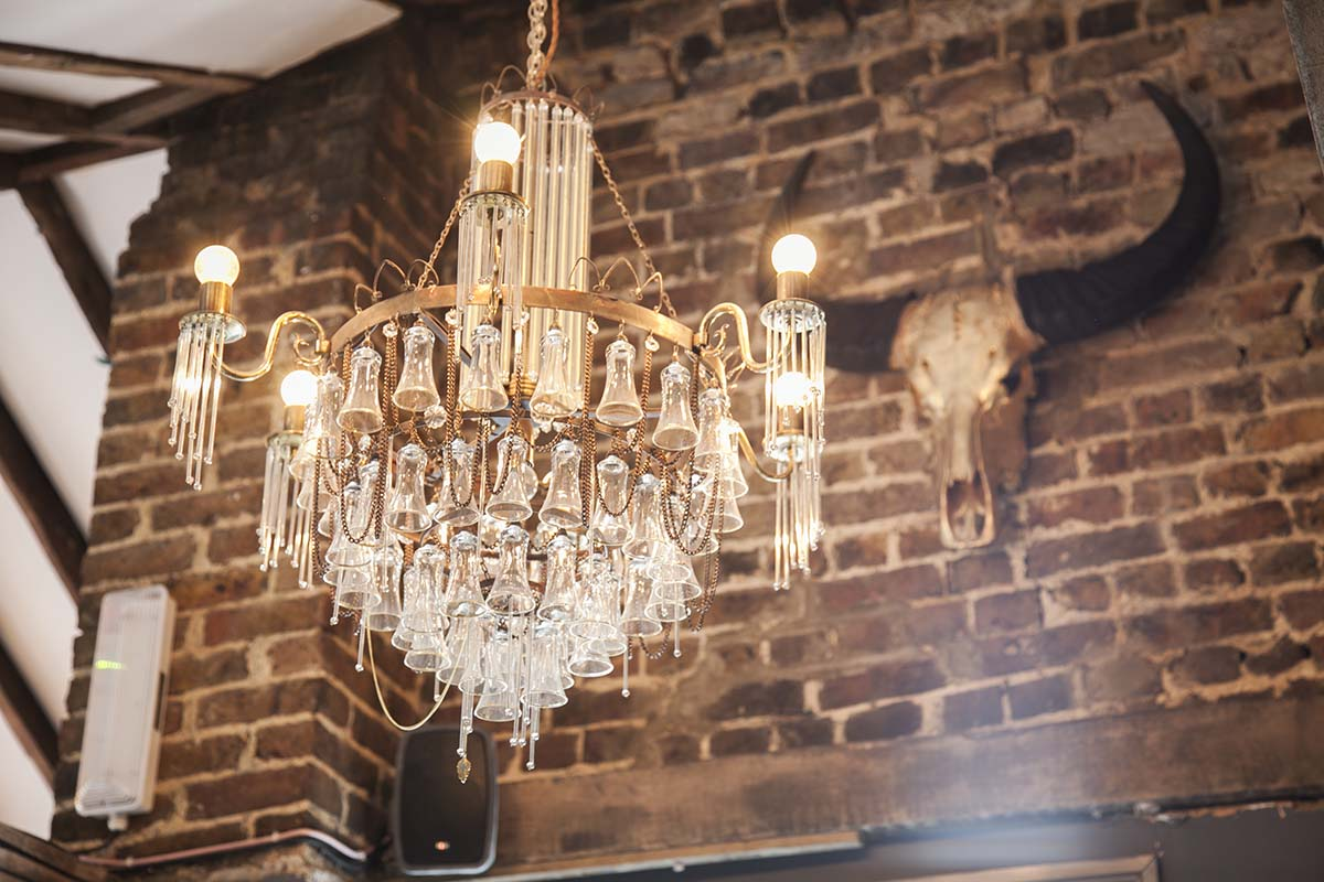 Attic bar featuring custom made Ambrosia chandelier made from liquor glasses.