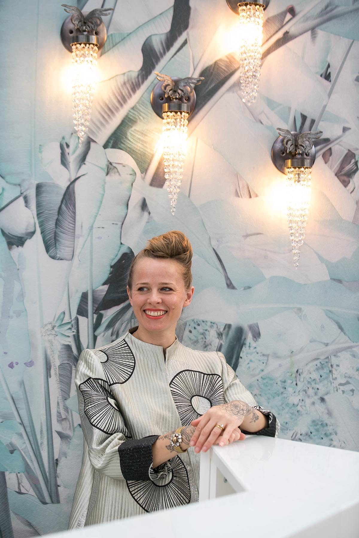 Fiona Gall from Emerald Faerie lighting brand at the VIP & Press room reception desk. Featuring her Birds of Paradise wall lights and Elli Popp's wallpaper